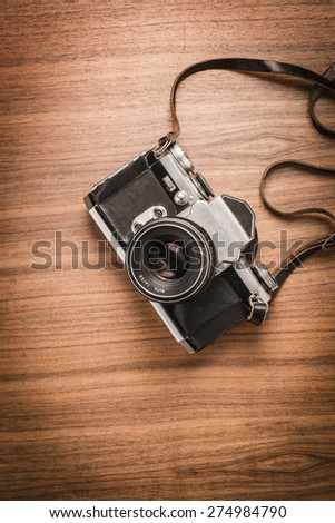 Top view of old retro 35 mm film camera lying on wooden table. Photographic nostalgia with old-fashioned photo equipment. Concepual image of old technology with a vintage look.
