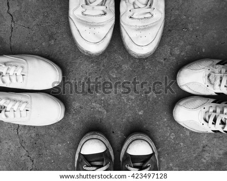 Top view of old sneaker shoes on floor background with black and white style - stock photo