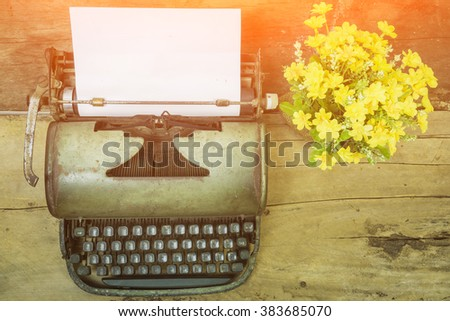 top view of Old typewriter with blank paper,retro typewriter on table ,Retro typewriter placed on wooden planks, typewriter and a blank sheet of paper and flower pot ,vintage tone,selective focus. - stock photo