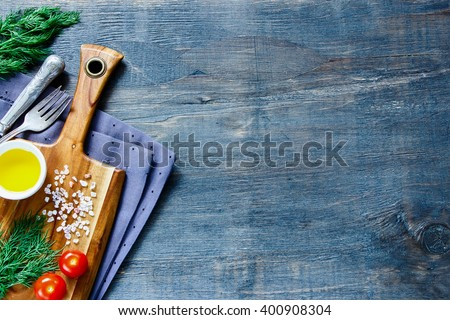 Top view of old wooden kitchen table with cutting board and ingredients on vintage background, place for text. - stock photo