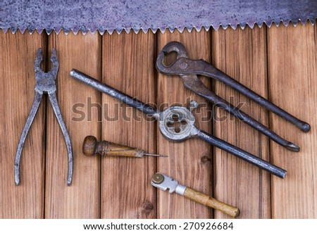 Top view of old working tools: pliers, hammer, saw, awl, glass on wooden background - stock photo