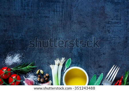 Top view of olive oil and fresh cooking ingredients (young green onions, peppercorns, tomatoes, garlic, rosemary) on dark vintage background. Top view. Cooking, Healthy Eating or Vegetarian concept. - stock photo
