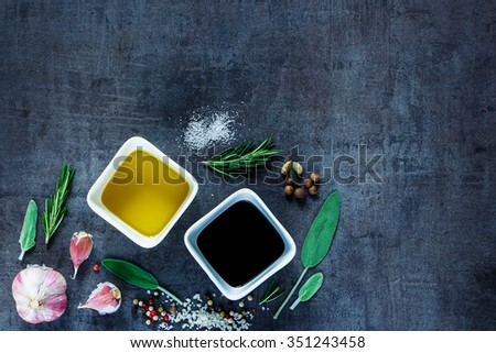 Top view of Olive oil and vinegar with peppercorns, sea salt, garlic and rosemary on dark vintage background. Herbs and spices selection. Cooking, Healthy Eating or Vegetarian concept. - stock photo