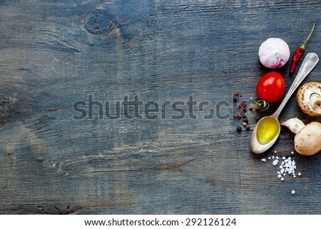 Top view of olive oil, mushrooms and tomatoes on dark wooden background with space for text. Vegetarian food, health or cooking concept. - stock photo