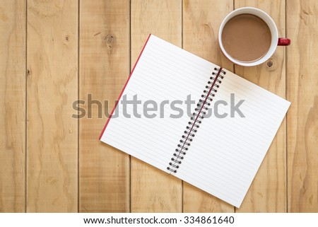 Top view of open book and coffee cup on wooden table background - stock photo