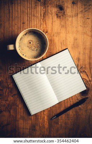 Top view of open notebook with blank pages, writing pencil and cup of coffee on old wooden desk, retro toned image - stock photo