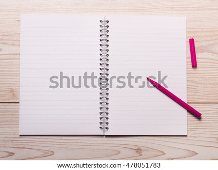 Top view of open notebook with pink marker on wooden desk