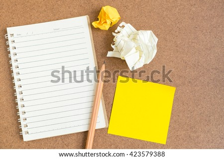 Top view of open spiral notebook, empty line paper with brown pencil and yellow sticky notes and crumpled paper ball - notebook paper on brown background - stock photo
