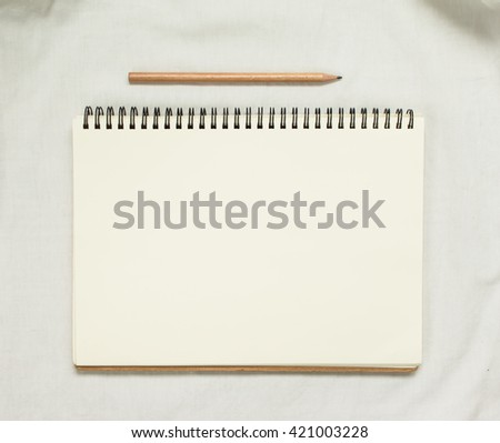 Top view of opened  empty notebook and wooden pencil on white fabric background.