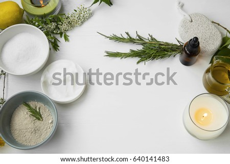 Top view of organic spa skincare products with salt, clay powder,olive oil,candle, flowers, essential oil,face cream, towels and pumice stone