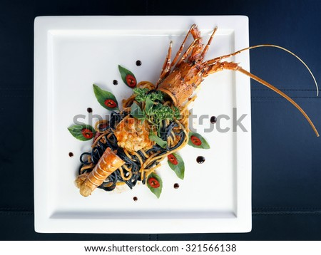 Top view of Pan fried two tone spaghetti with lobster on white plate, Thai style. - stock photo