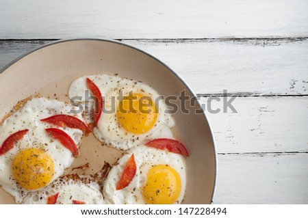 top view of pan with fried eggs and small pieces of tomato on the table - stock photo