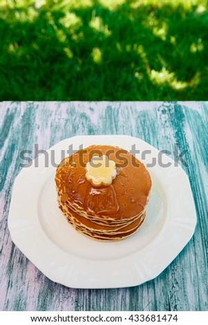Top view of pancakes with butter and honey on white plate on blue wooden background.  Pancakes with maple syrup. - stock photo
