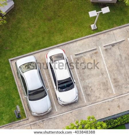 Top view of parking area with small garden in modern building  - stock photo