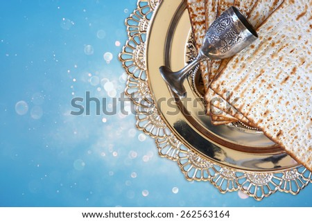 top view of passover background. matzoh (jewish passover bread) and traditional sedder plate over blue glitter background  - stock photo