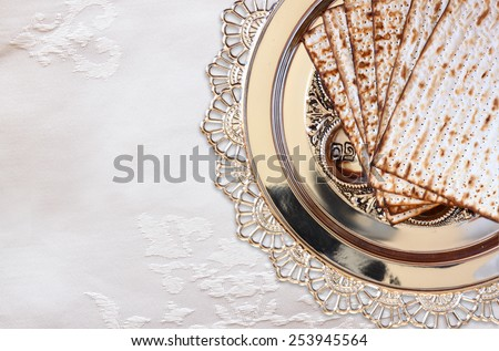 top view of passover background. matzoh (jewish passover bread) and traditional seder plate over white tablecloth background - stock photo