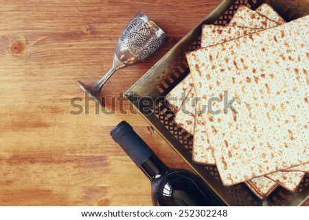 Top view of passover background. wine and matzoh (jewish holiday bread) over wooden board.