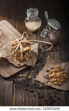 Top view of peanut biscuits, chocolate drops and jars with jam and condensed milk made in the dark tonality - stock photo