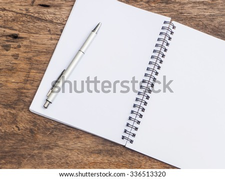 Top view of pen and notepad on wooden background - stock photo