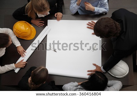 Top view of people around table in construction business meeting - stock photo