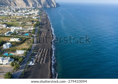 Top view of Perissa beach on the Greek island of Santorini with sunbeds and umbrellas. Beach is covered with fine black sand, and drops off sharply into the water. - stock photo