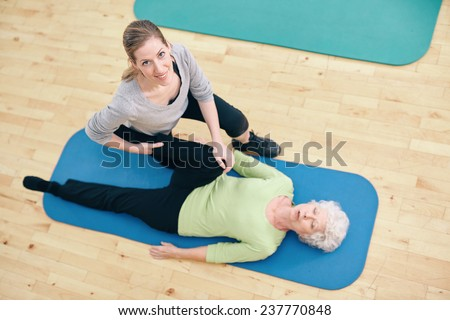 Top view of physical therapist helping senior woman do leg stretches at health center. Gym trainer assisting elder woman in leg stretching workout. - stock photo