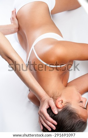 Top view of physiotherapist doing visceral spine treatment on woman.