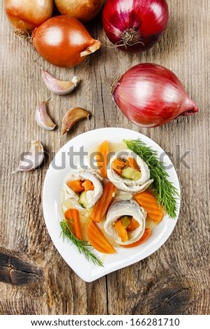 Top view of pickled herring rolls with vegetables on brown wooden background. Fresh onions and garlic. - stock photo