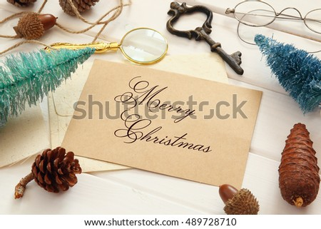 Top view of pine cones, greeting card, christmas tree and vintage objects on white wooden background