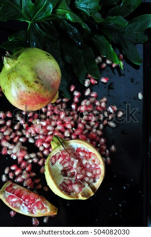 Top view of pink pomegranate with seed on black background
