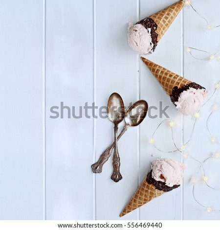 Top view of pink strawberry ice cream in waffle cones shot over a square rustic wooden background with fairy lights and antique spoons.