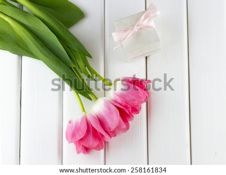 Top view of pink tulips and gift box with bow on white wooden background - stock photo