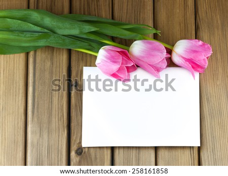 Top view of pink tulips with white sheet of paper on wooden background - stock photo