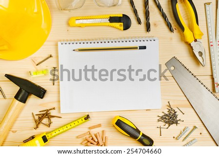 Top View of Planning a Project in Carpentry and Woodwork Industry Concept, Notebook and Assorted Woodwork and Carpentry Tools on Pinewood Workshop Table. - stock photo