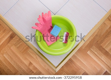 Top view of plastic basin with cleaning tools on tiled floor - stock photo