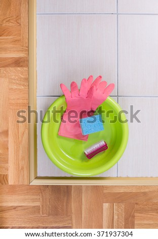 Top view of plastic basin with clening tools on tiled floor - stock photo