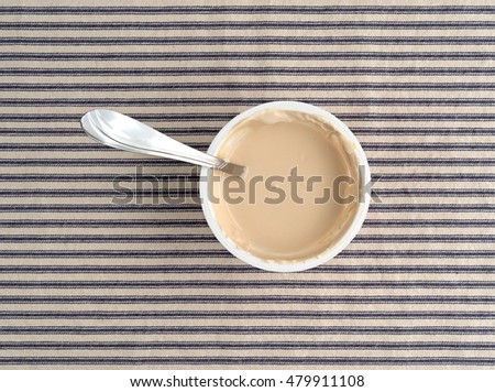 Top view of plastic container of coffee flavored yogurt with a spoon inserted into the food atop a striped tablecloth.