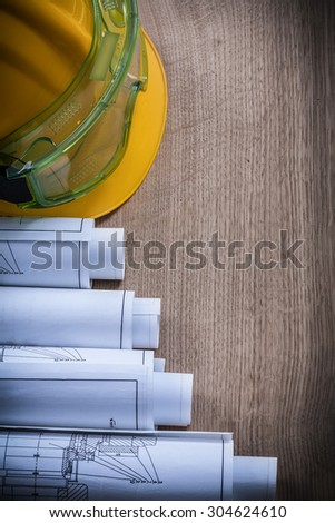 Top view of plastic goggles construction plans and safety cap. - stock photo