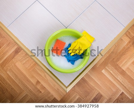 Top view of plastic washbasin with foam and cleaning tools on tiled floor - stock photo