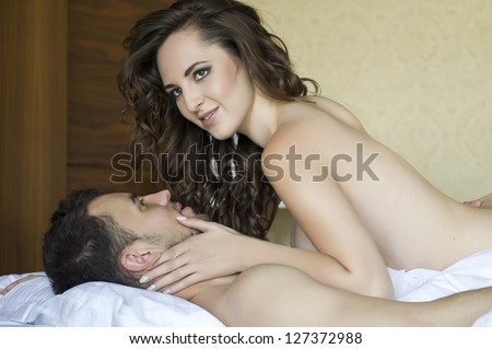 Top view of playful young couple enjoying in bed