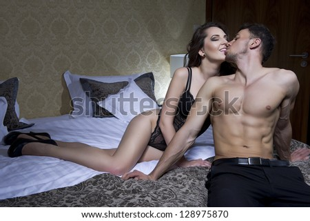 Top view of playful young couple enjoying in bed - stock photo