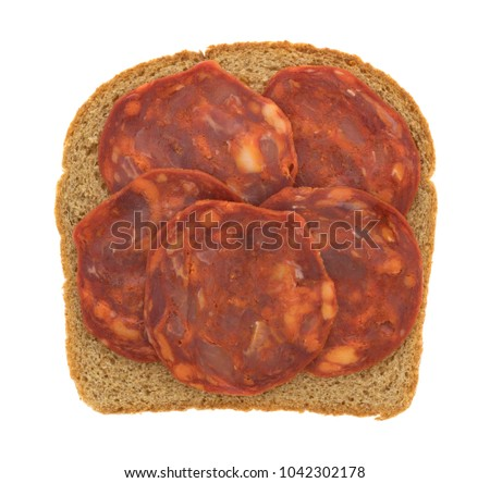 Top view of pork sausage slices on wheat bread isolated on a white background.