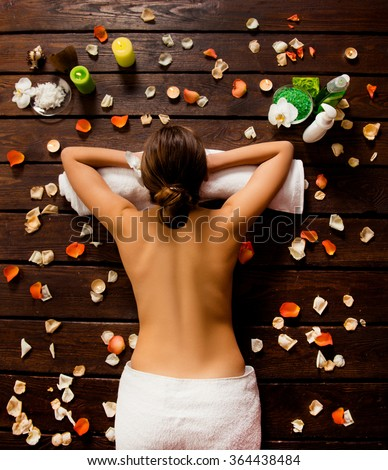 Top view of pretty woman laying in spa salon - stock photo
