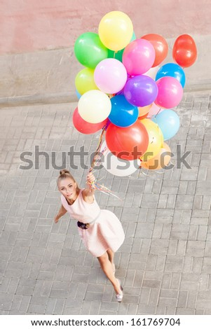 top view of pretty young girl in pink dress holding a bunch of balloons - stock photo