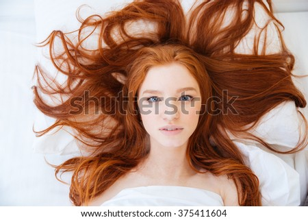 Top view of pretty young woman with beautiful long red hair lying in bed  - stock photo