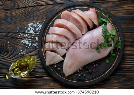 Top view of raw chicken breast fillet in a rustic wooden setting