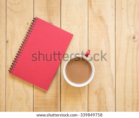 Top view of red book and coffee cup on wooden table background - stock photo