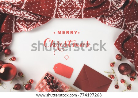 "top view of red christmas decorations with winter scarf, christmas balls, present and envelope, isolated on white with ""Merry christmas"" lettering"