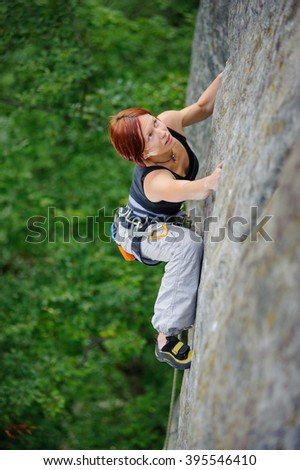 Top view of red-haired athletic woman climbing steep cliff wall in summer time looking to the top. Sport and healthy lifestyle concept. Climbing equipment - stock photo