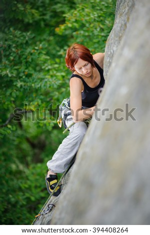 Top view of red-haired athletic woman climbing steep cliff wall in summer time. Sport and Healthy lifestyle concept. Climbing equipment - stock photo